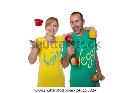 A vegetarian and a vegan with peppers and dumbbells made of vegetables - stock photo