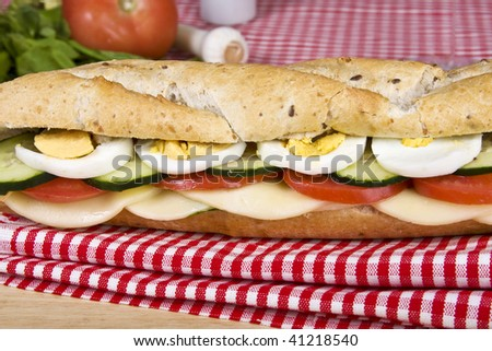 A vegetarian flax seeds baguette with cheese, tomato, cucumber and eggs. - stock photo