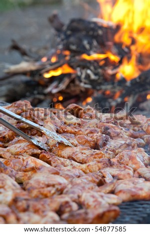 A vertical close up of chicken pieces being grilled on an open fire outdoors