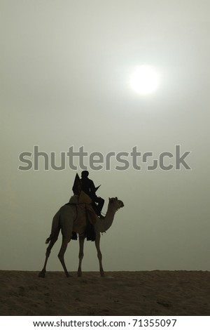 A vertical silhouette of a Tuareg rider and camel with bright sun - stock photo