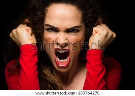 A very angry aggressive woman is clenching her fists in rage - stock photo