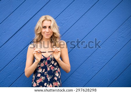 A very attractive woman stands in front of an wooden bright blue wall. She is putting on her sunglasses. She is a California girl with long blond hair. - stock photo