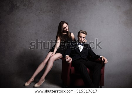 A very beautiful woman is posing with a handsome man in the dark studio in different clothes