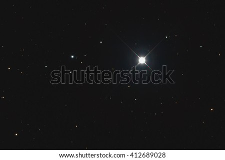 A very bright white star named Procyon or Alpha Canis Minors in the constellation Canis Minor taken with CCD camera and medium focal length telescope - stock photo