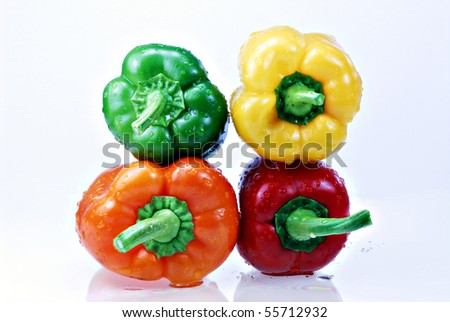 A very close up view of a fresh yellow, green, red, and orange capsicum