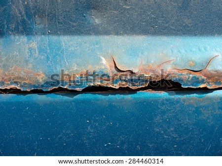 A very close view of a rusting rocker panel of an old car. - stock photo
