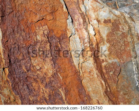 A very close view of a weathered colorful rock formation.