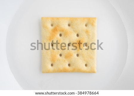 A very close view of an unsalted saltine cracker on an off white plate. - stock photo