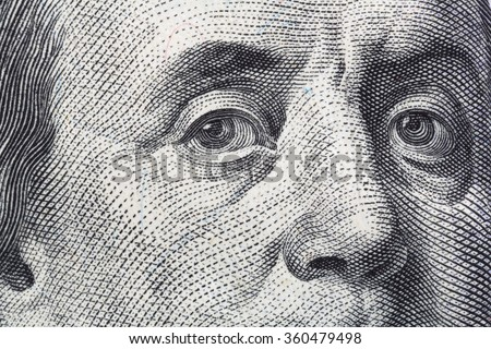 A very close view of the portrait of Benjamin Franklin on a hundred dollar American bill. - stock photo