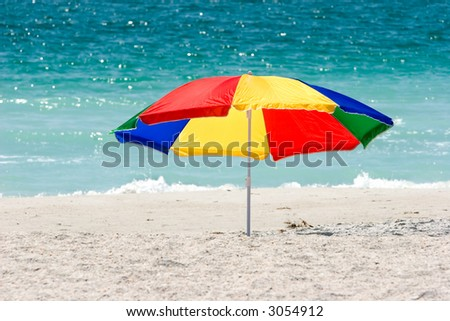 A very colorful beach umbrella on the public beach in Treasure Island, Florida. - stock photo