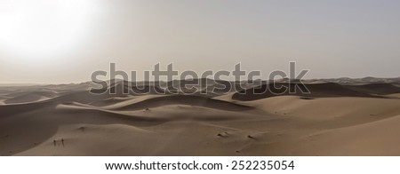 A very contrasted view of a sea of brown sand dunes in the Sahara desert in Erg Chegaga in Morocco in Morocco in the spring during a hot sunny day with te sun burning in the corner. - stock photo