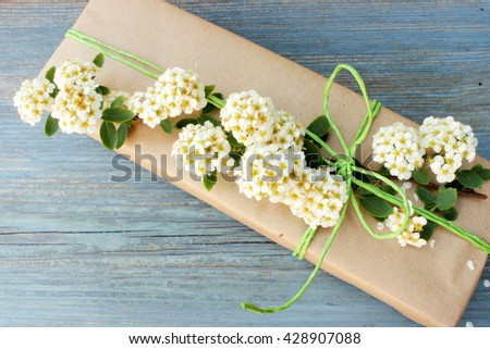 A very cute and tender gift box wrapped with simple brown craft paper and decorated with fresh natural flowers. Floral decor elements. Romantic, dreaming style.