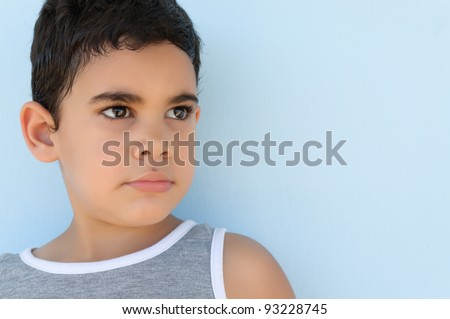 A very cute latin boy looking towards a side - stock photo