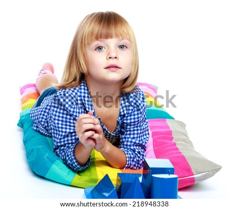 a very cute little girl lying on colorful pillows isolated on white background.Education concept happy child. - stock photo
