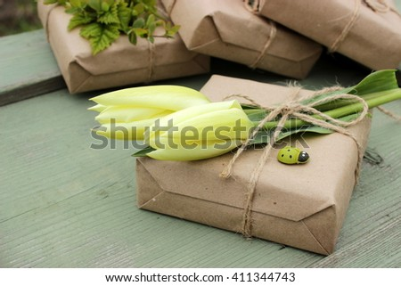 A very cute small gift box wrapped with craft paper and jute decorated with natural white tulips, and green wooden ladybirds