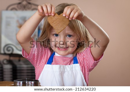 A very cute young boy is holding a love-heart shaped ginger bread cookie he is baking. - stock photo