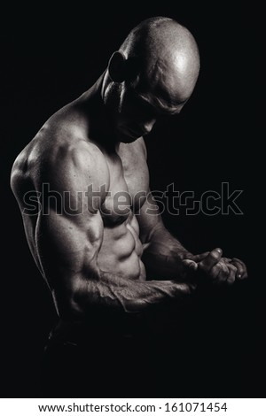 a very fit shirtless young man flexing hs muscles