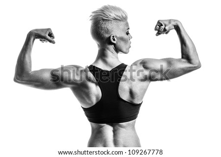 a very fit woman posing her muscular body - stock photo