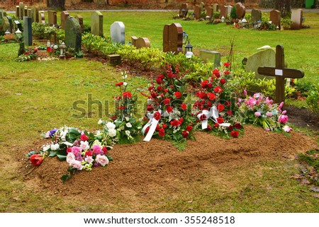 A very fresh grave at a cemetery. A wooden cross with a white paper note for a name is a temporary headstone. Lovely flowers adorn the small pile of soil on top of the grave. Weather is damp. - stock photo