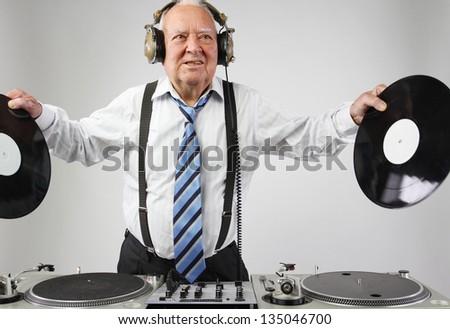 a very funky elderly grandpa dj mixing records - stock photo