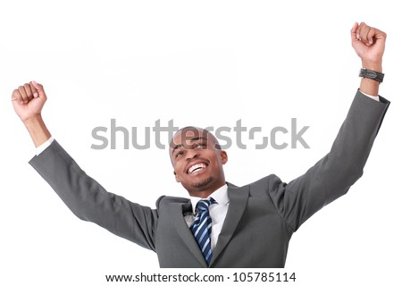 A very happy and attractive african businessman wearing a corporate grey suit and blue tie punching the air with his fists arms in air, smiling and shouting in victorious success for his business deal