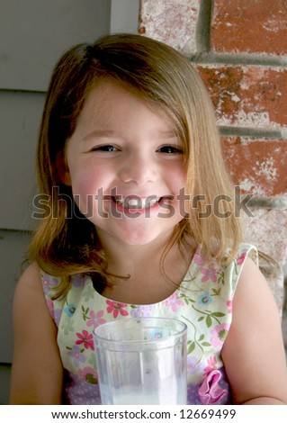 A very happy and very healthy girl holds a fresh glass of milk - stock photo