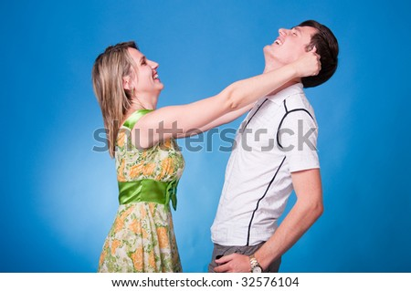 A very happy couple having fun in studio on blue background - stock photo