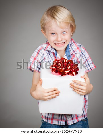 A very happy cute young boy holding a large gift or present and smiles at camera. - stock photo