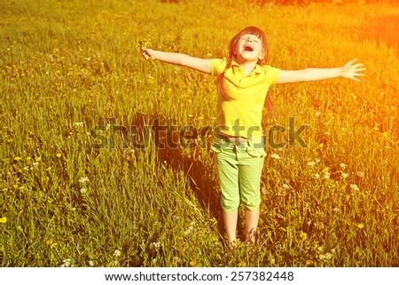 a very happy little girl with a bouquet of flowers in hands on background of green grass. child outdoors with dandelions