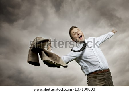 A very happy young man. It turns your joy taking off his jacket and turning it in the air. - stock photo