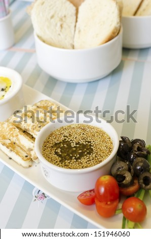 A very healthy Lebanese breakfast with bread, zaatar spread, hallumi cheese, olives and tomatoes. Very typical dish of lebanon and Mediterranean cuisine. - stock photo