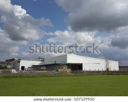 a very large building under construction sky is cloudy - stock photo