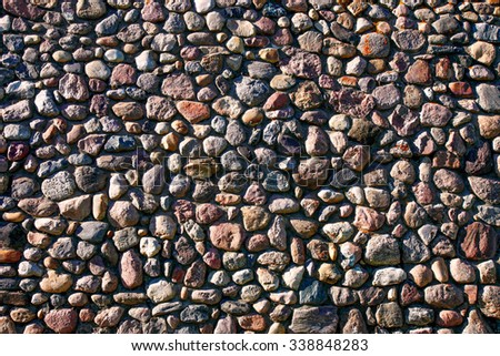 A very large wall of many different rocks and stones illuminated by sunlight.