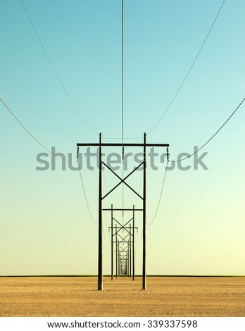 A very long row of electrical poles and electricity power lines disappear over the horizon. - stock photo