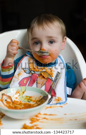 A very messy cute eight month old child trying to eat orange colored pasta