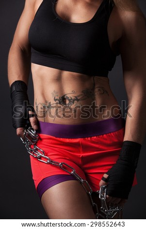 A very muscular girl is holding a chain in her hands. Detail shot of belly muscles with side light.