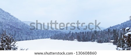 A very nice view of the mountains and of the little houses on the lake shore. This is a dream location. - stock photo