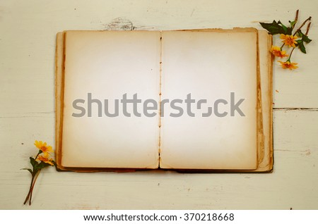 A very old book with stained pages is open, providing copy space, laying on a white washed, rustic wooden table. Flat lay perspective. Flowers decorate edges. Vintage filter applied. - stock photo
