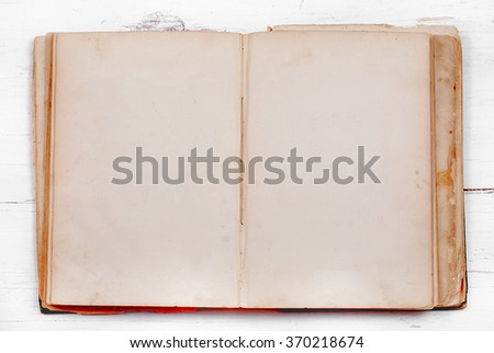 A very old book with stained pages is open, providing copy space, laying on a white washed, rustic wooden table. Flat lay perspective with horizontal composition. - stock photo