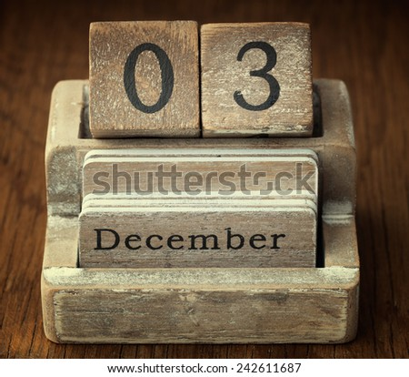 A very old wooden vintage calendar showing the date of 3rd December on wood background