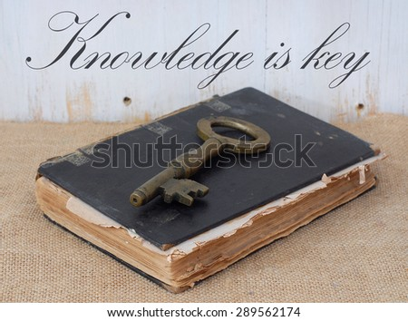 A very old, worn book laying on burlap in front of a rustic wooden wall. Concept of knowledge being the key to success or ancient mysteries are contained inside. Message about knowledge added. - stock photo