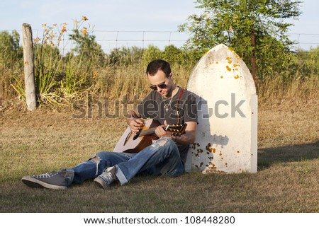 A very sad young man leaning against the head stone of a loved one while playing a guitar and missing them. - stock photo
