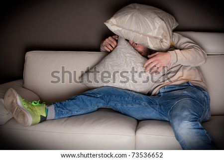 A very scared man watching a horror movie at home - stock photo