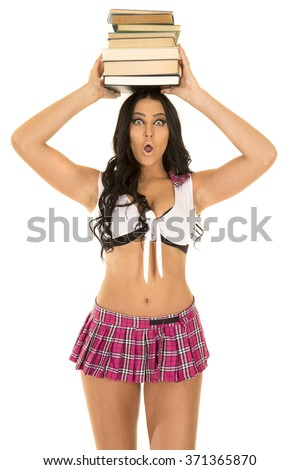 A very sexy school girl with a shocked expression holding books on her head. - stock photo