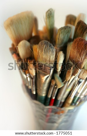 A very shallow depth-of-field image of used paintbrushes stacked in a glass vase. Focus is on the front brushes. - stock photo