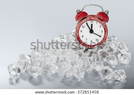 A very small red alarm clock inserted between ice crystals. Clock showing five to twelve. Useful for your time or stress concepts. - stock photo