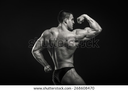 A very strong man on a dark background. Male bodybuilder. - stock photo