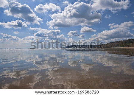 A very strong reflection of the sky across the beach at Charmouth in Dorset, England - stock photo