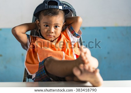 a very young student boy at school sits like a bos on the chair. Feet on the table. Thai school in a small village - stock photo