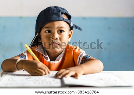 a very young student boy makes his exercise. Thai school in a small village - stock photo